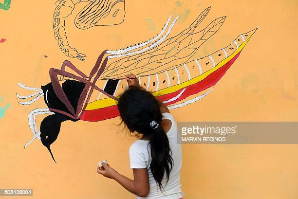 A girl paints a mural that educates people about a mosquito control project in the village of San Diego village in La Libertad Salvador on February 4...