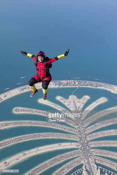 Girl parachute sit flying over the Dubai Palm