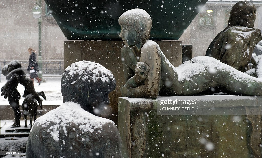 A girl passes a covered fountain during snowfall in Berlin on December 22 , 2012. Meteorologists forecast snow fall in northern and eastern parts of Germany.