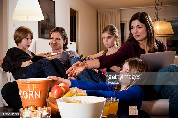 Girl passing popcorn bowl to mother with family sitting on sofa
