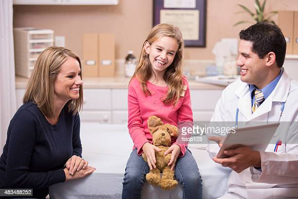 Girl patient with pediatrician doctor, mother. Latin descent. Digital tablet.