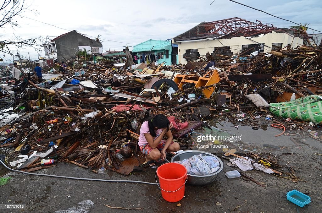 A girl pauses while washing clothes amongst the debris in an area devastated by Typhoon Haiyan on November 12, 2013 in Leyte, Philippines. Four days after the Typhoon Haiyan devastated the region many have nothing left, they are without food or power and most lost their homes. Around 10,000 people are feared dead in the strongest typhoon to hit the Philippines this year.