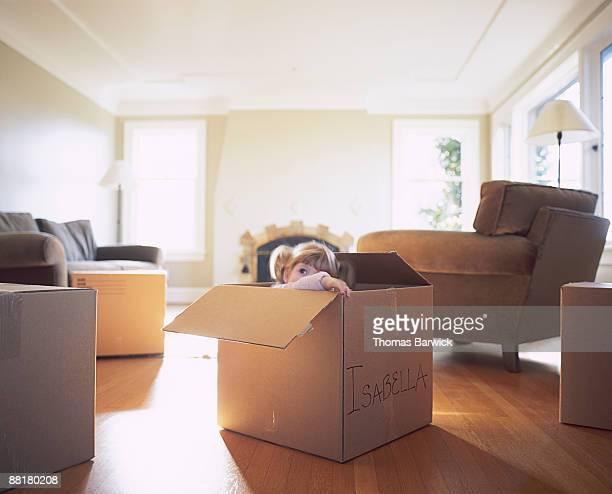 Girl peeking out of moving box