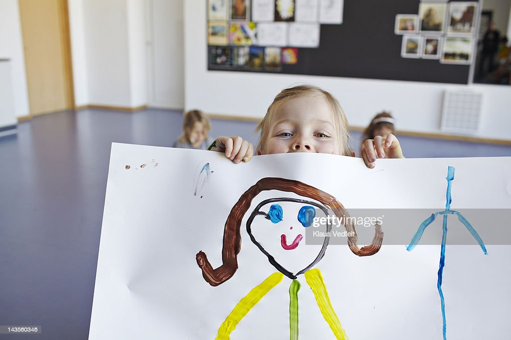 Girl peeking over her own drawing with smiley eyes : Stock Photo