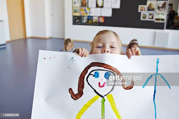 Girl peeking over her own drawing with smiley eyes