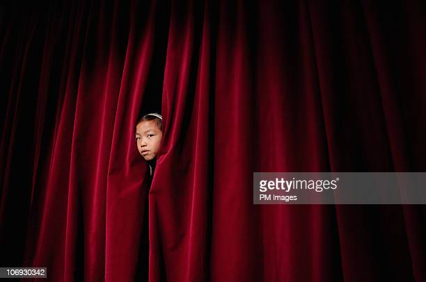 Girl peeking through curtain