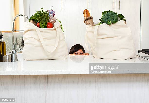 girl peering over counter with groceries