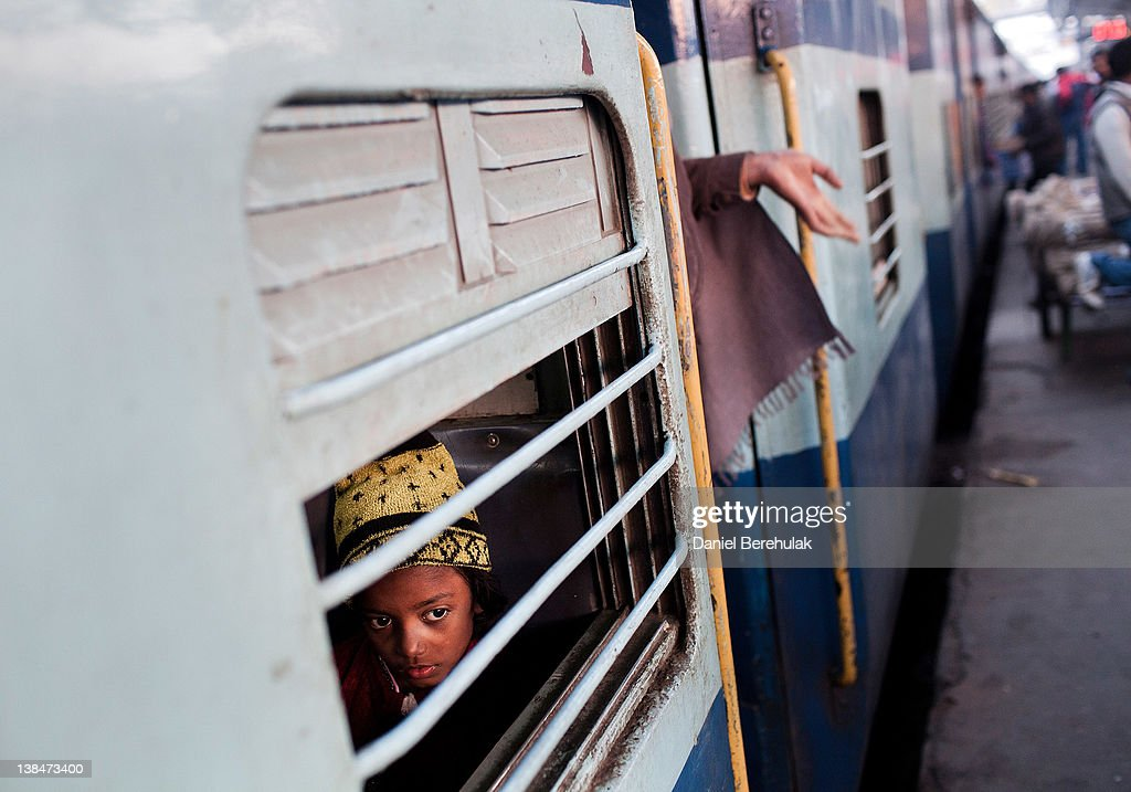 A girl peers out from a carriage at Nizamuddin Railway Station on February 07, 2012 in New Delhi, India. The Nizamuddin Railway Station serves as the main station connecting all major cities, and is served by Northern Railways. The state-owned Indian Railways runs 12,000 trains a day, covers 39,000 miles of track, employs 1.4 million people and is the world's second biggest rail network under single management.