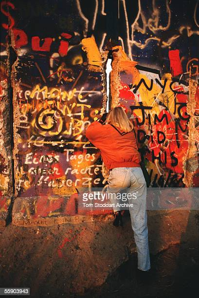 A girl peers through a gap in the Berlin Wall on the morning of November 10th 1989 the day the wall finally came down