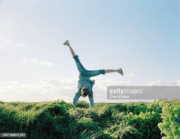 Girl (7-9) performing cartwheel outdoors