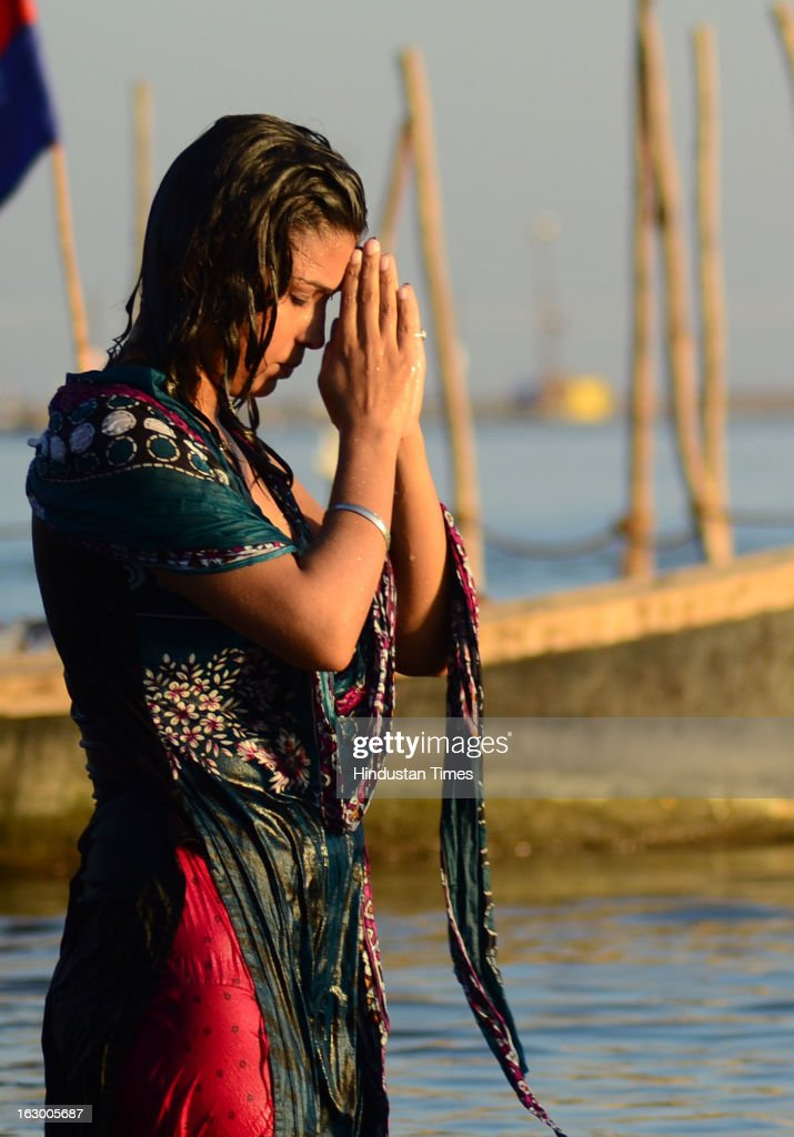 A girl performing surya namashkar on the bank of Sangam waters in the Kumbh Mela area on March 3, 2013 in Allahabad, India. The mega religious fair, held once in 12 years, last official bathing on 'Maha Shivratri' on March 10, 2013.