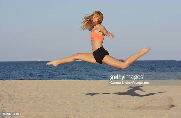 Girl performs acrobatic split jump on a beach