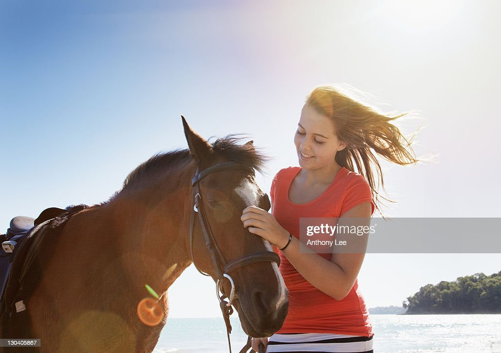 Girl petting horse outdoors : Stock Photo