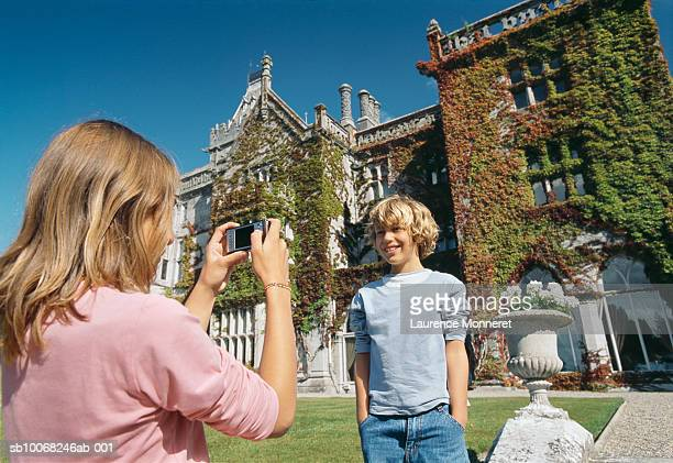 Girl (12-13) photographing boy (8-9) in front of castle