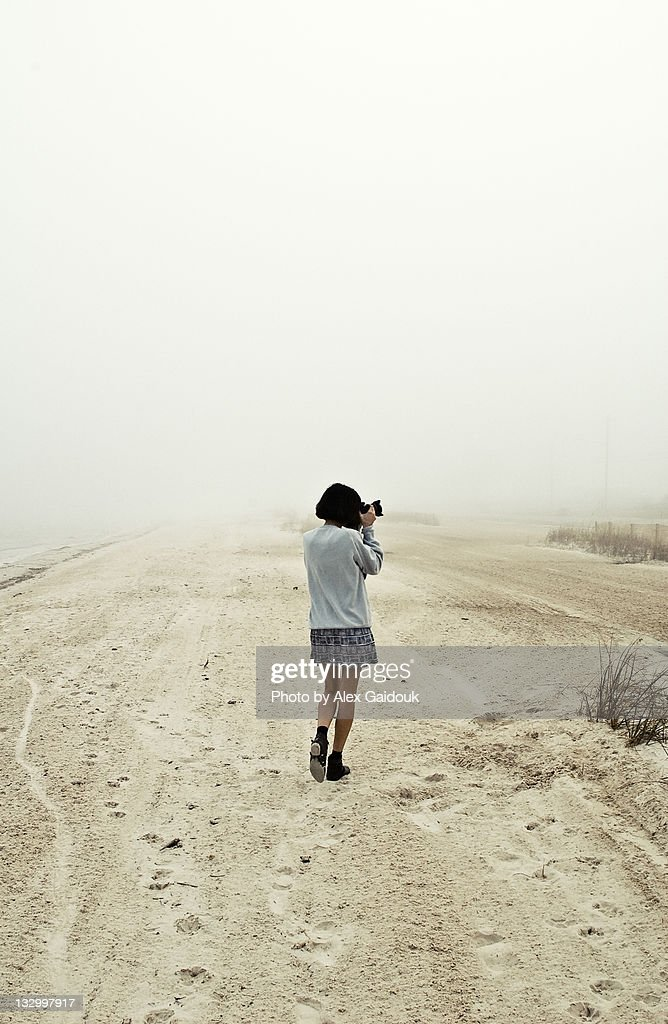 Girl photographing on beach
