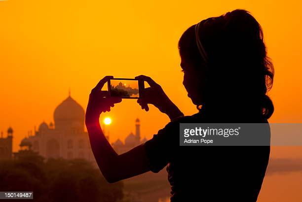 Girl photographing the Taj Mahal with a smartphone