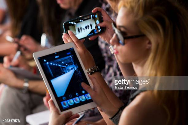 A girl photographs the Kingston University show on an iPad during day 3 of Graduate Fashion Week 2014 at The Old Truman Brewery on June 2 2014 in...