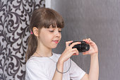 Cute and beautiful girl taking pictures with a compact camera.