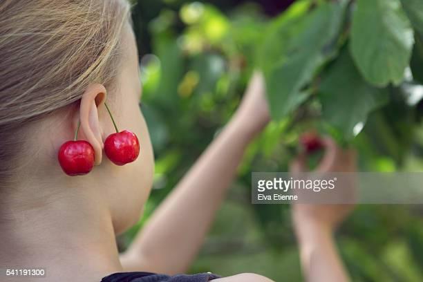 Girl picking fruit and wearing cherries as earrings