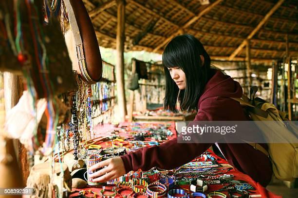 Girl picking handicrafts in African market