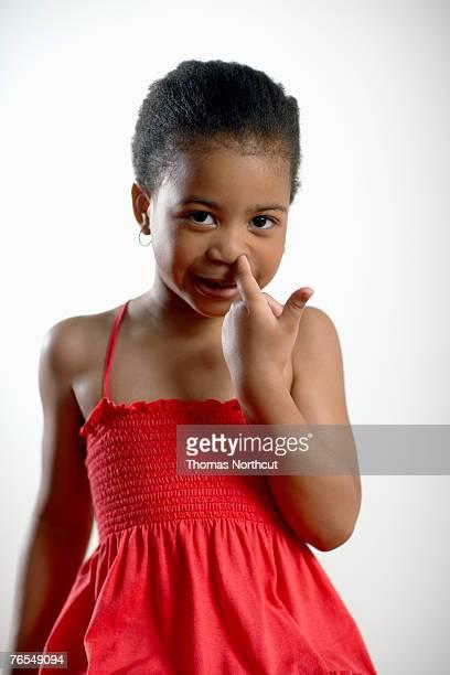 Girl (4-6) picking nose, portrait