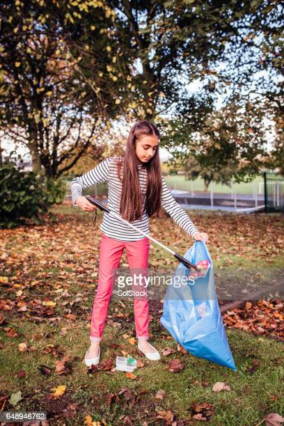 Girl Picking up Rubbish using a Grabber