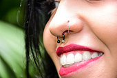 Girl with nose piercing with red baton smiling photo in super close up