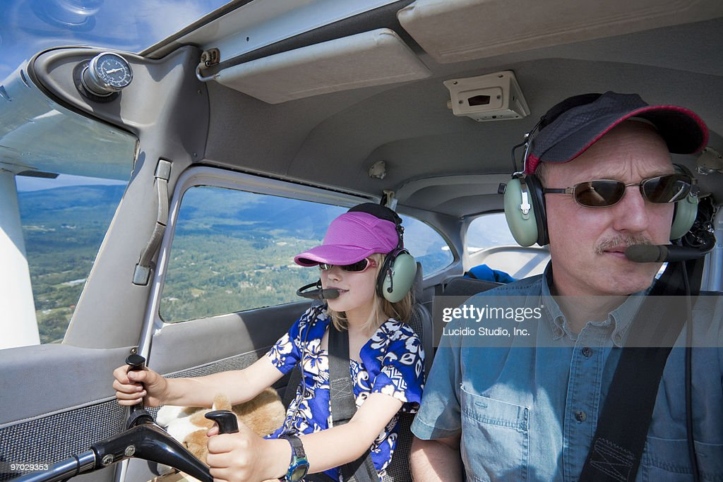 Girl piloting a plane with her dad : Stock Photo