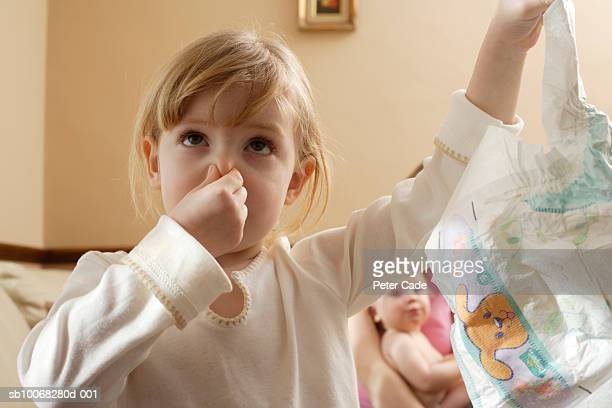 Girl (6-7) pinching nose holding nappy, close-up