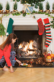 Girl placing festive items by fireplace