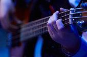 girl hands play bass guitar at a concert under blue soft light