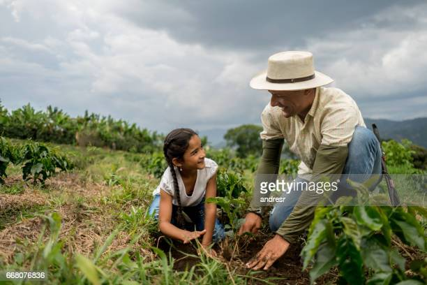Girl planting a tree with her father at the farm