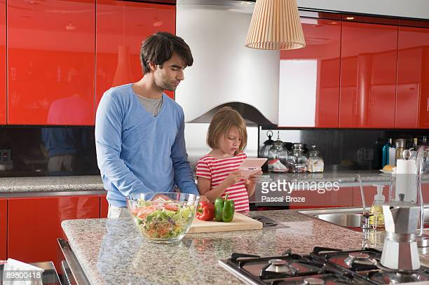 Girl playing a video game with her father chopping bell pepper beside her