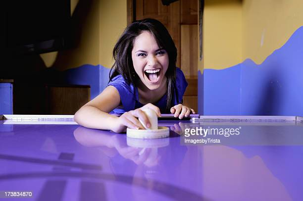 Girl playing air hockey in a purple table