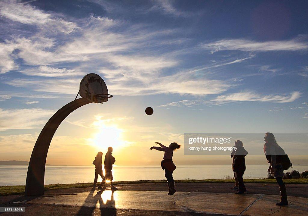 Girl playing basketball at sunset beach.
