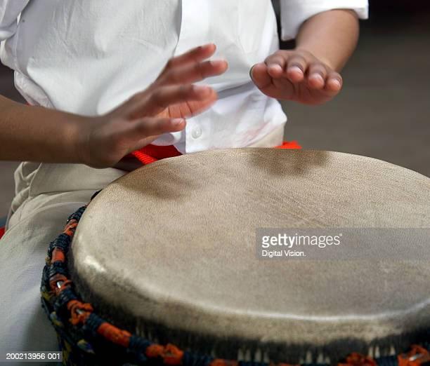 Girl (6-12) playing bongo drum, close-up