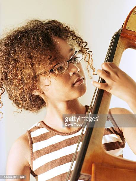 Girl (10-12) playing cello, close-up