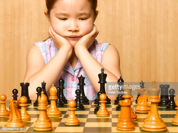 Girl (6-7) playing chess, sitting at chessboard with head in hands