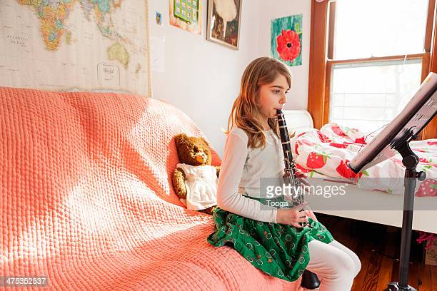 Girl playing clarinet in bedroom