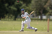 A girl batting as she plays in a cricket match