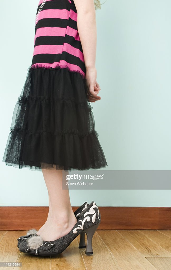 Girl (3-5) playing dress up in adult high heels : Stock Photo