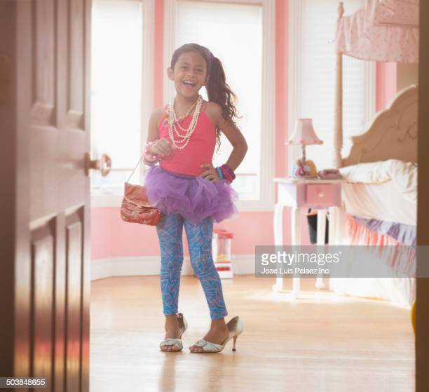 Girl playing dress up in bedroom