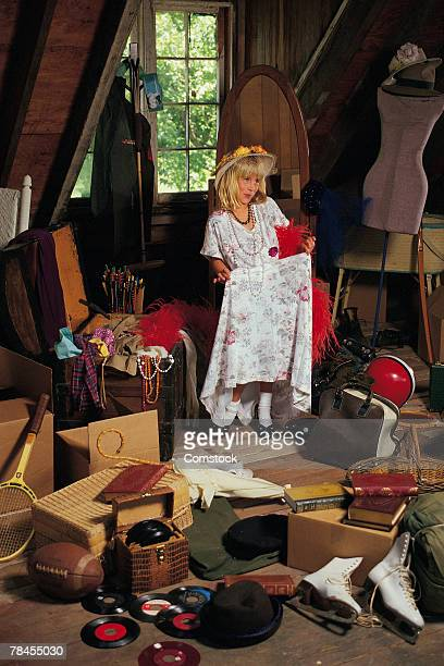 Girl playing dress-up in attic among memorabilia
