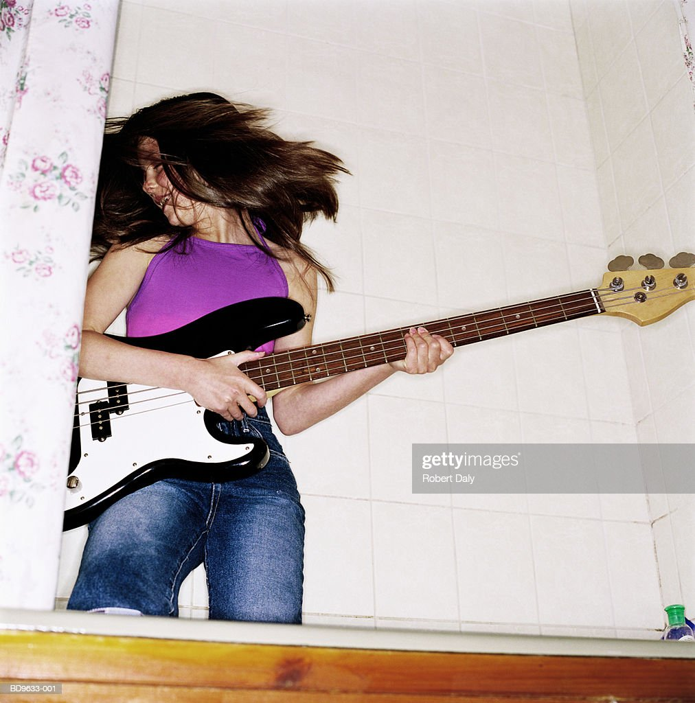 Girl (10-12) playing electric guitar in bathtub