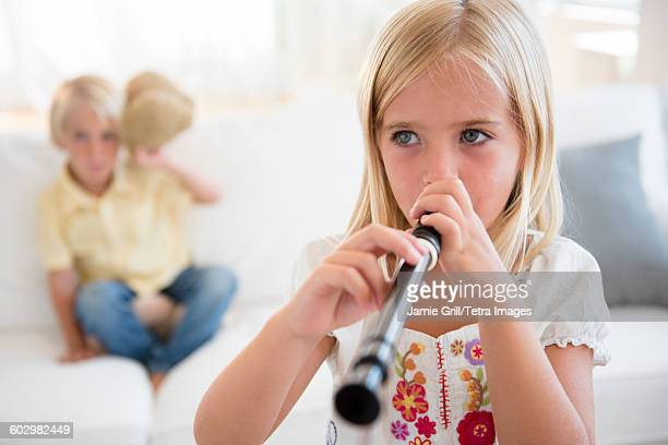 Girl (6-7) playing flute and boy (4-5) sitting on sofa