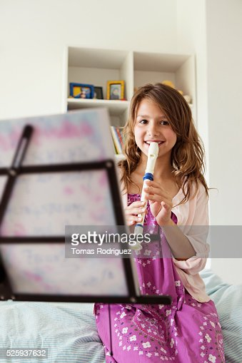 Girl (8-9) playing flute in bedroom : Foto de stock