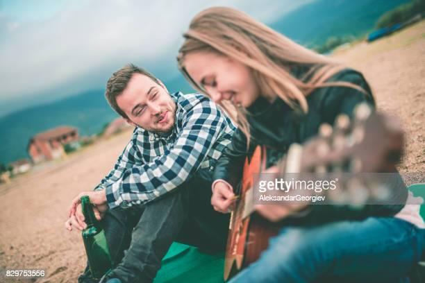 Fille jouant guitare et garçon bière boire, chanter et profiter