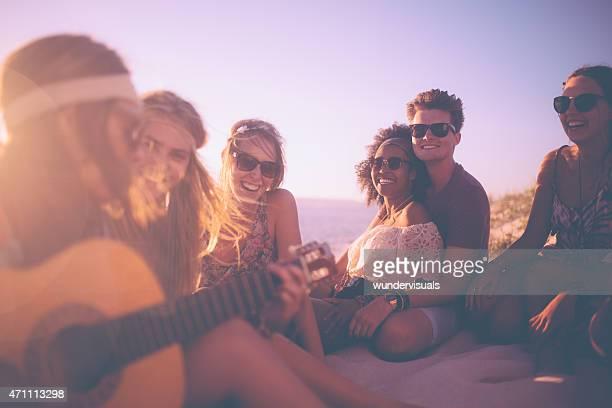 Fille jouant de la guitare pour ses amis à un beachparty