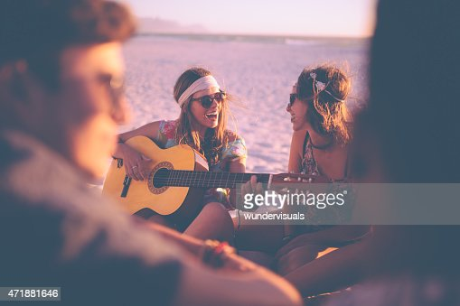 Girl playing guitar for her friends at a beachparty