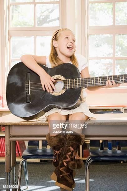 Girl playing guitar in classroom